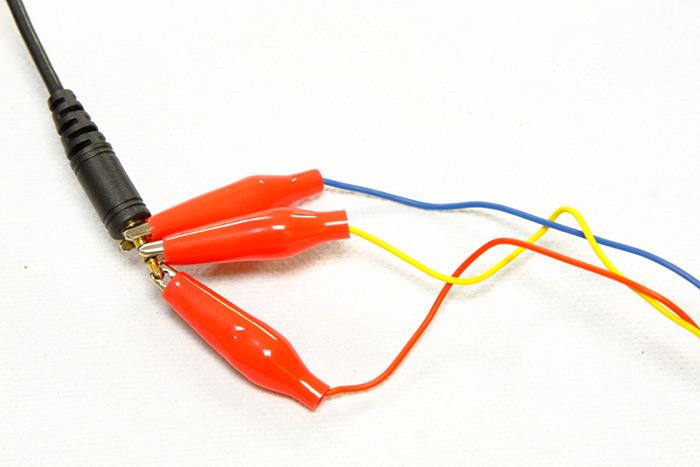 """Conectando las pinzas al conector Mini Jack de 2.5"""" de la cámara emisora."""
